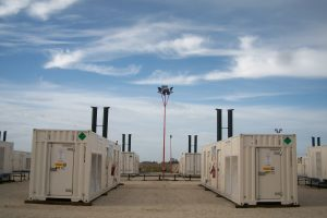 A group of power generators outside of a manufacturing plant.
