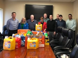 The O'Neal Manufacturing team takes a picture in front of their donation to Laundry and More.