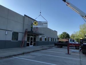 An O'Neal Manufacturing Sign being installed on a building.