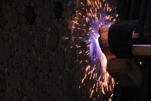 A plasma punch machine cutting a piece of metal.