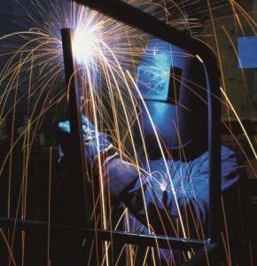 A man welding a piece of steel.