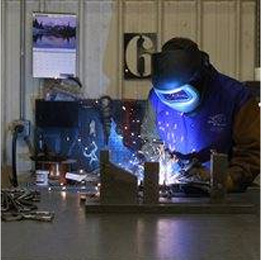 A man welding a piece of steel.